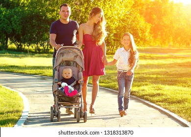 Happy active family walks in the summer park. beautiful long-haired mother her husband with her daughter and son in a stroller rest on the nature
