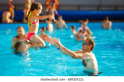 Happy active family young father and his cute daughter adorable toddler girl playing in a swimming pool jumping into the water enjoying summer vacation