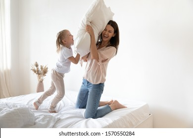 Happy active family young mother and cute small kid daughter laugh play pillow fight on cozy bed, carefree parent mum having fun with funny child at home bedroom enjoy morning leisure lifestyle game