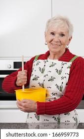Happy active grandma is baking cookies at home