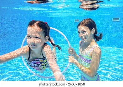 Happy active kids swim in pool and play underwater, girls diving and having fun, children on summer  vacation, sport concept