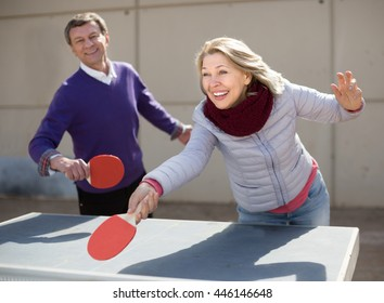 Happy active mature man and a woman playing table tennis