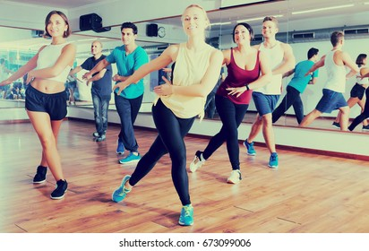 Happy active men and ladies dancing zumba at lesson