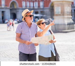 Happy active retired tourist couple searching for their location in Plaza Mayor Madrid in travel around Europe holidays retirement concept.