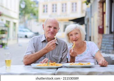 Happy active senior couple enjoying time together eating belgian french fries in outdoors street cafe on a summer day in typical European town - active retirement concept
