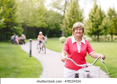 Happy active senior woman riding bike in park at summer