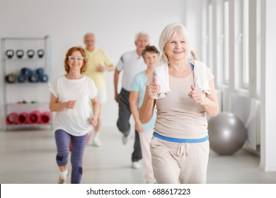 Happy active seniors exercising together in white spacious room