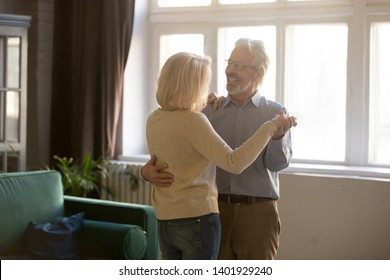 Happy active sixty years old spouses standing in living room moving, grey-haired husband embraces blond wife aged couple dancing waltz celebrating life event, romantic mood dating of retirees concept