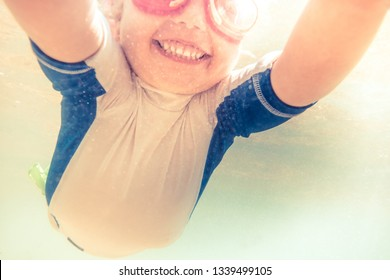 Happy active smiling child toddler swimming underwater during summer beach holidays vacation
