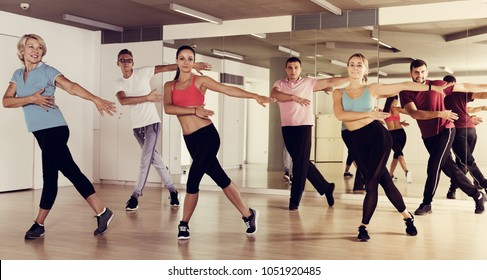 Happy active sporty adults of different ages dancing at dance class
