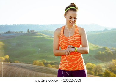 happy active woman jogger in fitness clothes with headphones setting sport tracker against scenery of Tuscany, Italy.