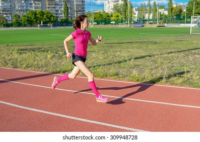 Happy active woman running on track, sprinting and working out on stadium, sport and fitness in city, urban background