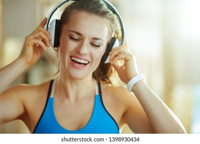 happy active woman in sport clothes listening to the music with headphones in the modern house.
