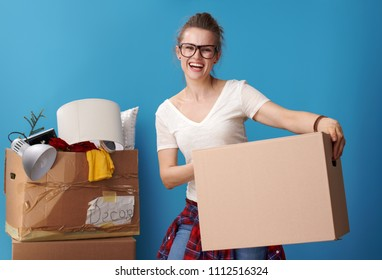 happy active woman in white shirt holding a neat cardboard box and an untidy cardboard box in the background on blue