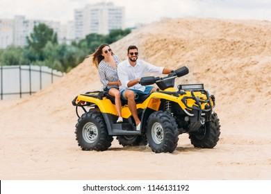 happy active young couple riding all-terrain vehicle in desert