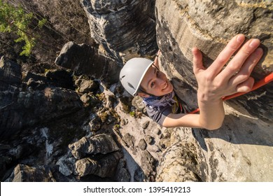 Happy active young girl rock climbing on sandstone towers - reaching the summit, Tisa sandstone rocks, Usti nad Labem region, Czech republic