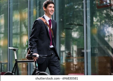 Happy active young man wearing business suit while walking to the job after bicycle commuting