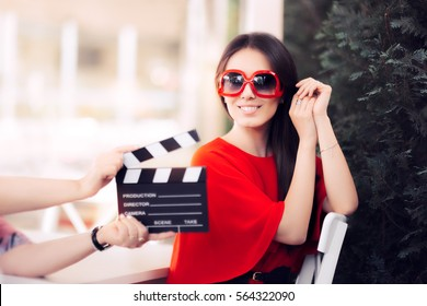 Happy Actress with Oversized Sunglasses Shooting Movie Scene - Diva in red dress and big shades starring in an artistic film