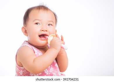 Happy adorable 9 months Asian baby learning to brush teeth, isolated on white
