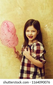Happy, adorable girl, small, little, child in plaid dress smiling with delicious, pink, cotton candy, sweet, sugar, spun candyfloss, on stick on beige background. Unhealthy food or snack