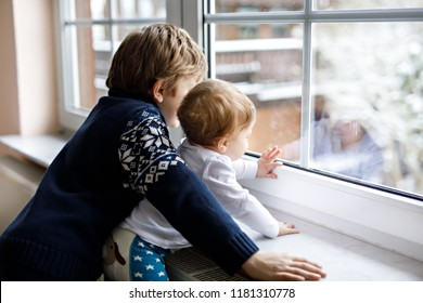 Happy adorable kid boy and cute baby girl sitting near window and looking outside on snow on Christmas day or morning