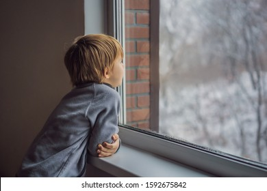 Happy adorable kid boy sitting near window and looking outside on snow on Christmas day or morning. Smiling child fascinated with snowfall and big snowflakes