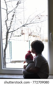Happy adorable kid boy sitting near window and looking outside on snow on Christmas day or morning.  Child fascinated with snowfall and big snowflakes. Child hugging toy Snowman in front of window