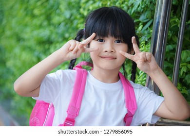 Happy adorable little asian girl showed victory sign with pink school backpack when she went to school