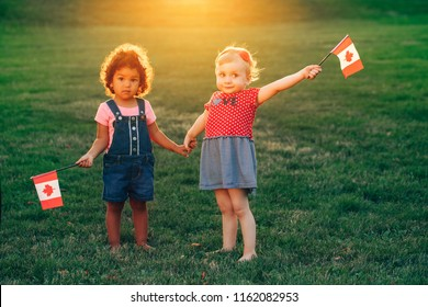 Happy adorable little blond Caucasian and hispanic latin girsl smiling holding hands and waving Canadian flags in park outdoors. Multiracial children celebrating Canada Day. Flag Day concept.