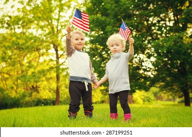 Happy adorable little blond Caucasian girl and boy smiling laughing holding hands and waving American flag outside  celebrating 4th july,  Independence Day, Flag Day concept
