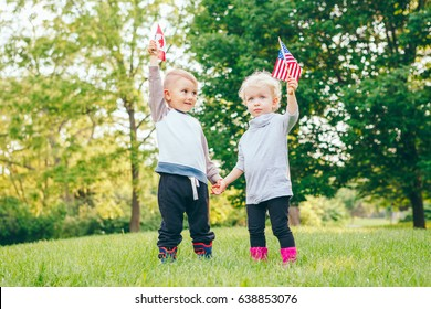 Happy adorable little blond Caucasian girl and boy smiling laughing holding hands and waving American and Canadian flags, outside in park, celebrating 4th july Independence Day