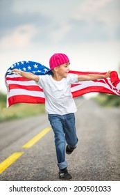Happy adorable little boy smiling and waving American flag outside in motion. Smiling child celebrating 4th july - Independence Day