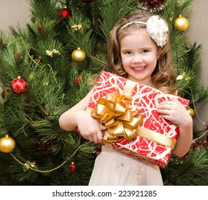 Happy adorable little girl with gift box near christmas tree