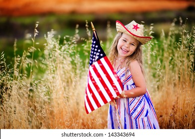 Happy adorable little girl smiling and waving American flag outside, her dress with strip and stars, cowboy hat. Smiling child celebrating 4th july - Independence Day
