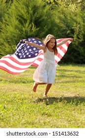 Happy adorable little girl smiling and waving American flag outside/Smiling child celebrating 4th july - Independence Day