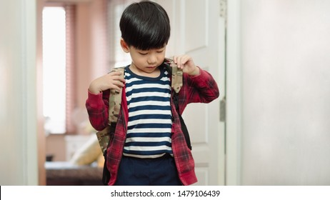 Happy and adorable little preschool Asian boy puts on school bag after preparing books and things, get ready to school. Montessori, Daily routine, Self Care, Practical Life Skills, Child Development.
