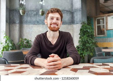 Happy adult bearded redhead man sitting at table in coffee shop and smiling at camera