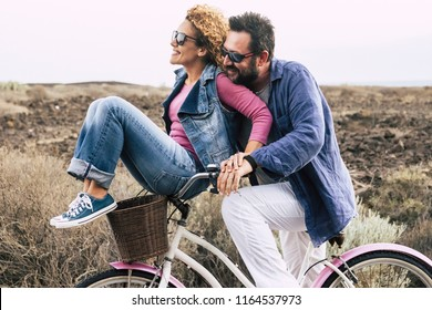 happy adult caucasian, couple having fun with bicycle in outdoor leisure activity. concept of active playful people with bike during vacation - everyday joy lifestyle withouth age limitation -