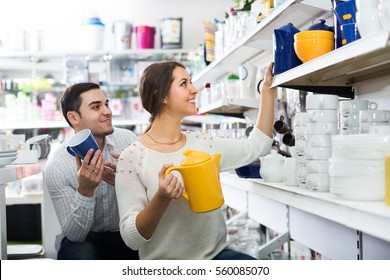 Happy adult couple buying ceramic ware in the shop