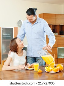 Happy adult couple having breakfast with juice in morning at home interior