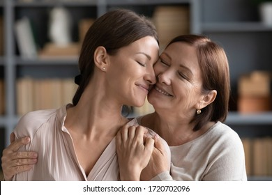 Happy adult daughter and mature mother hugging close up, expressing love and care, touching cheeks, smiling young woman enjoying tender moment with older middle aged mum, standing at home
