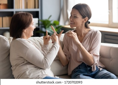 Happy adult daughter and older mother speaking sign language, having fun, sitting on sofa at home, smiling young woman and mature mum chatting, communicating, showing gestures, deaf family