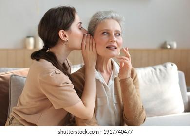 Fröhliche erwachsene Tochter flüstert ihrer mittleren Mutter zu Hause Geheimnisse zu, tratscht und teilt geheim. Schöne Frau, die gute Neuigkeiten von reifer Mutter, vertraute Beziehungen.