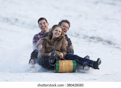 Happy adult family enjoying some winter fun on a toboggan.