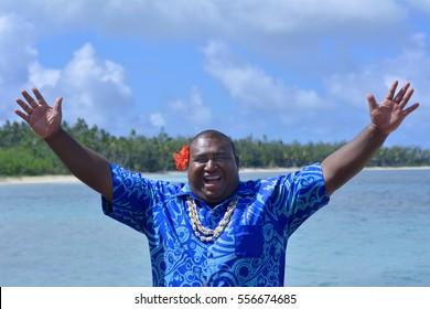 Happy adult Fijian man greeting in Fijian language Bula,(general greeting hello) against The Blue Lagoon on Nanuya Lailai Island on of the Yasawa Islands of Fiji. Real people. Copy space