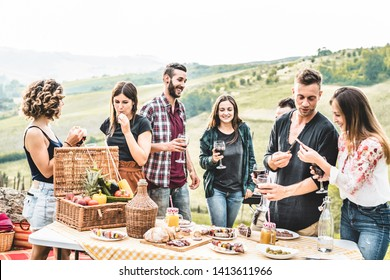 Happy adult friends eating at picnic lunch in italian vineyard outdoor - Young people having fun on gastronomic weekend tuscany tour - Friendship, summer and food concept - Focus on center guys