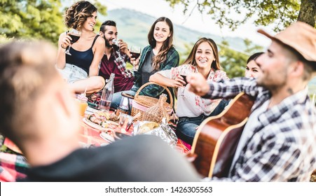 Happy adult friends eating at picnic lunch in vineyard outdoor - Young people having fun on gastronomic weekend tour - Friendship, summer and food concept - Focus on  center blond girl