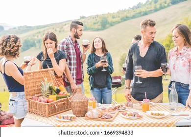 Happy adult friends eating at picnic lunch in italian vineyard outdoor - Young people having fun on gastronomic weekend tuscany tour - Friendship, summer and food concept - Focus on right man face