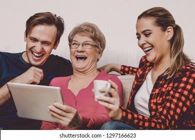 Fröhliche erwachsene Kinder mit älteren Mutter auf einem Sofa, mit Tablet-Computer. Das Tageskonzept der Mütter.