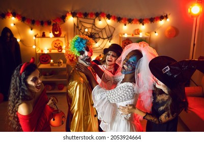 Happy adult male and female friends having fun at crazy indoor Halloween fancy dress party in dark room with light decor. Dead Bride fooling around and jokingly choking and suffocating funny clown guy